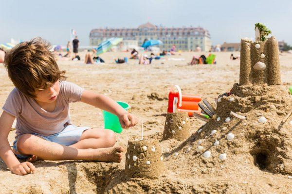 Enfant et chateau de sable sur la plage de Deauville