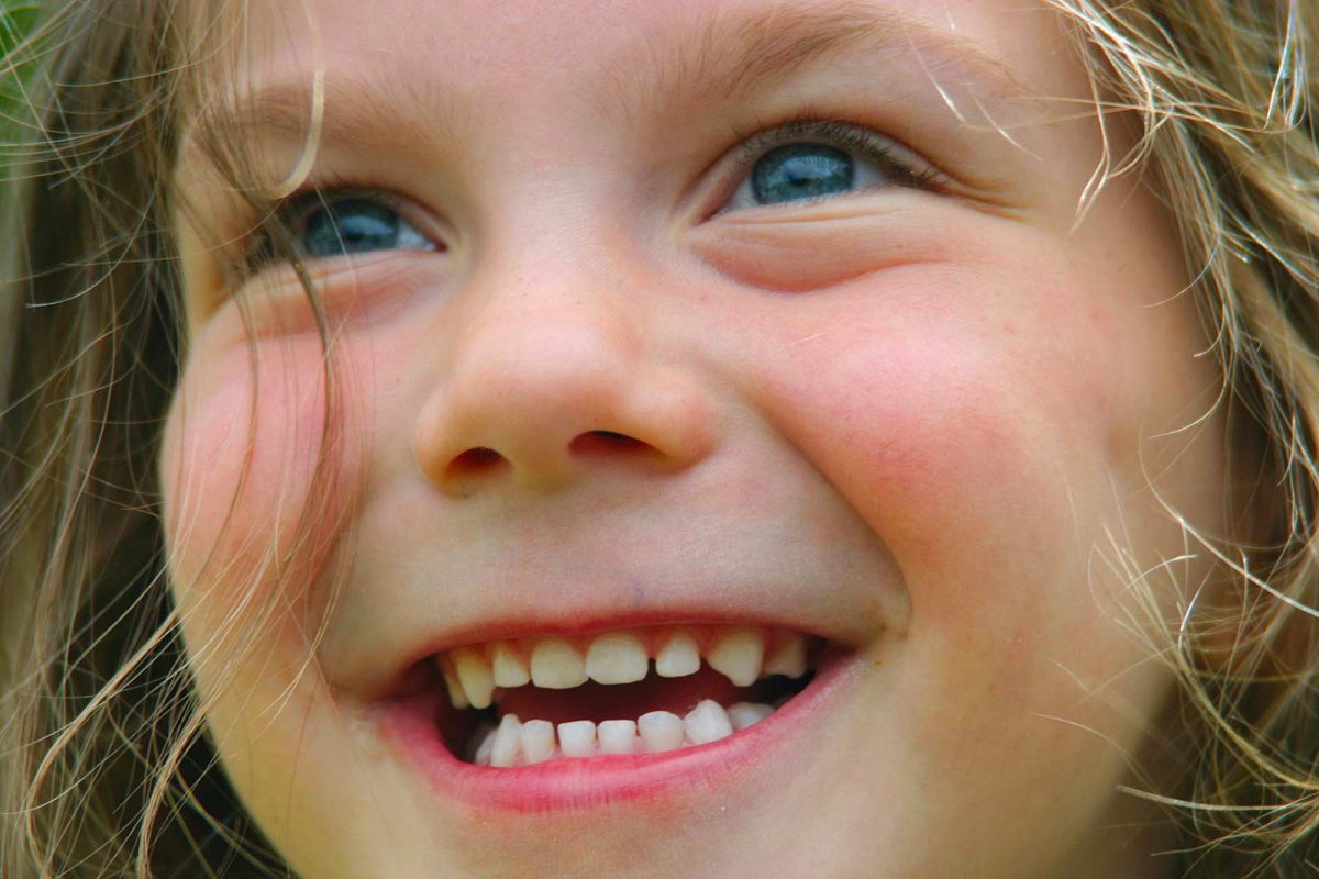 Visage souriant d'une petite fille qui regarde un feu d'artifice
