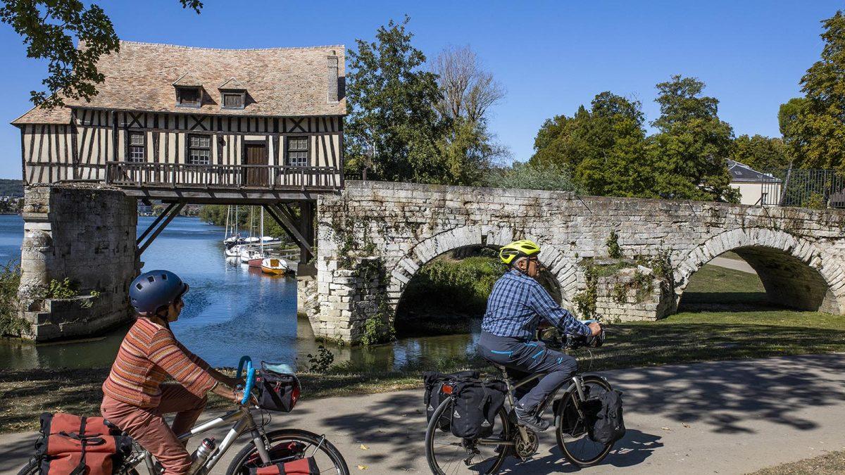 couple à vélo devant le vieux moulin de Vernon - La Seine à vélo