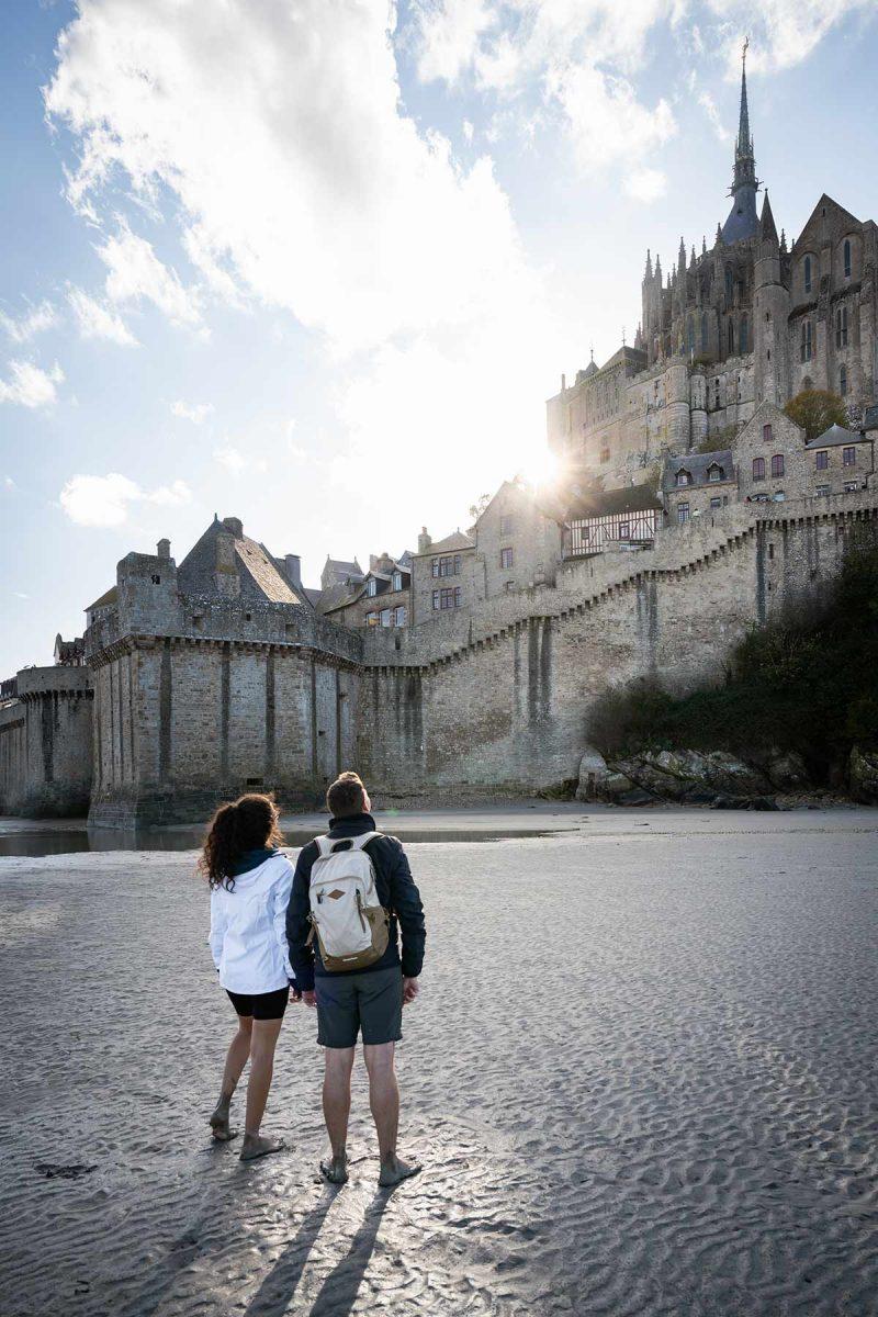 Couple marchant sur le sable devant le Mont-Saint-Michel